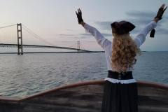 Good-Fortune-pirate-lady-with-arms-raised-in-front-of-Mackinac-Bridge